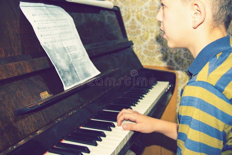De jongen bestudeert snaren op nota's, zittend bij de piano royalty-vrije stock fotografie