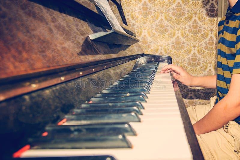 De jongen bestudeert snaren op nota's, zittend bij de piano royalty-vrije stock afbeeldingen