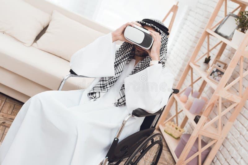 De jongen bevindt zich achter een Arabische mens in een rolstoel die virtuele werkelijkheidsglazen onderzoekt stock afbeelding