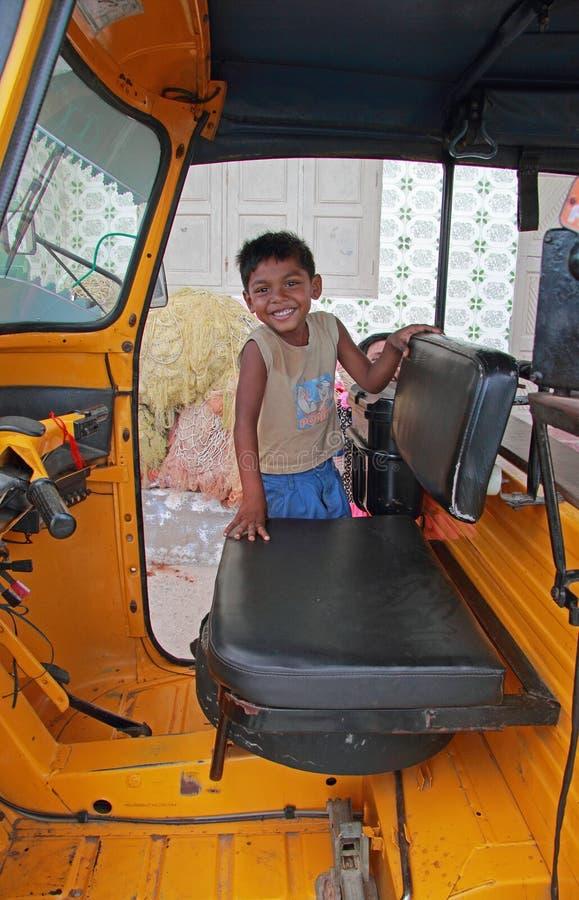 De jongen bevindt zich in cabine van Indische taxi stock afbeeldingen