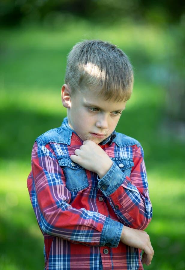 De jongen bevindt zich denkend tegen het groen royalty-vrije stock foto's
