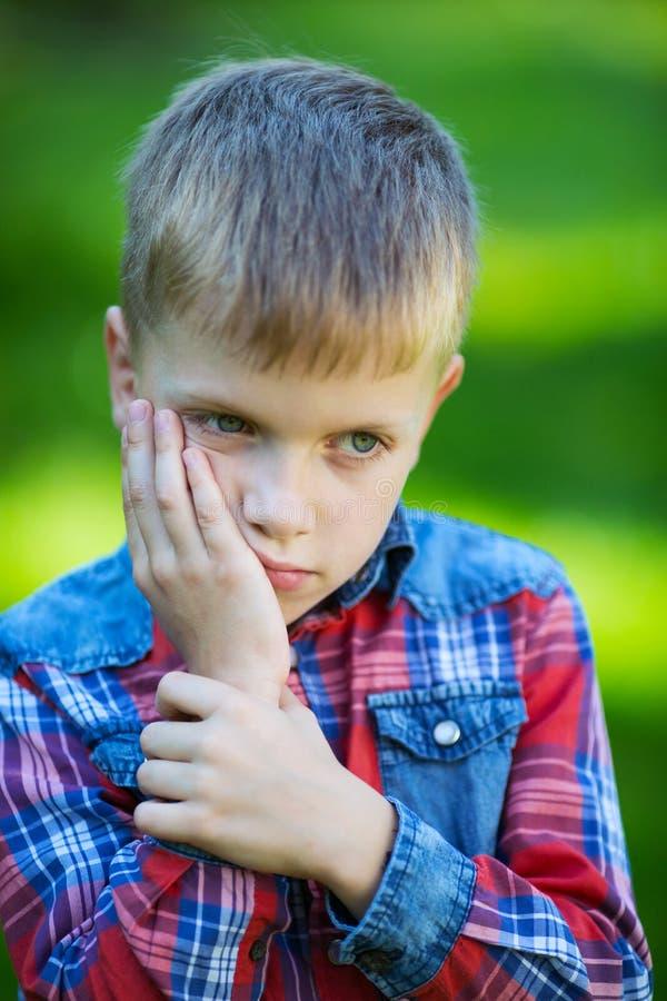 De jongen bevindt zich denkend tegen het groen royalty-vrije stock fotografie
