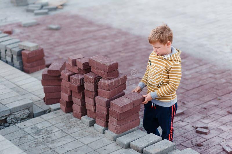 De jongen bevindt zich dichtbij de de bouwbakstenen Grijze en rode bakstenen Kinderen en beroepen Kinderen en bouw royalty-vrije stock afbeeldingen