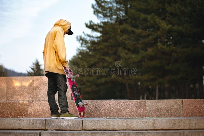 De jongen bevindt zich met een skateboard in de zonsonderganglichten royalty-vrije stock afbeelding