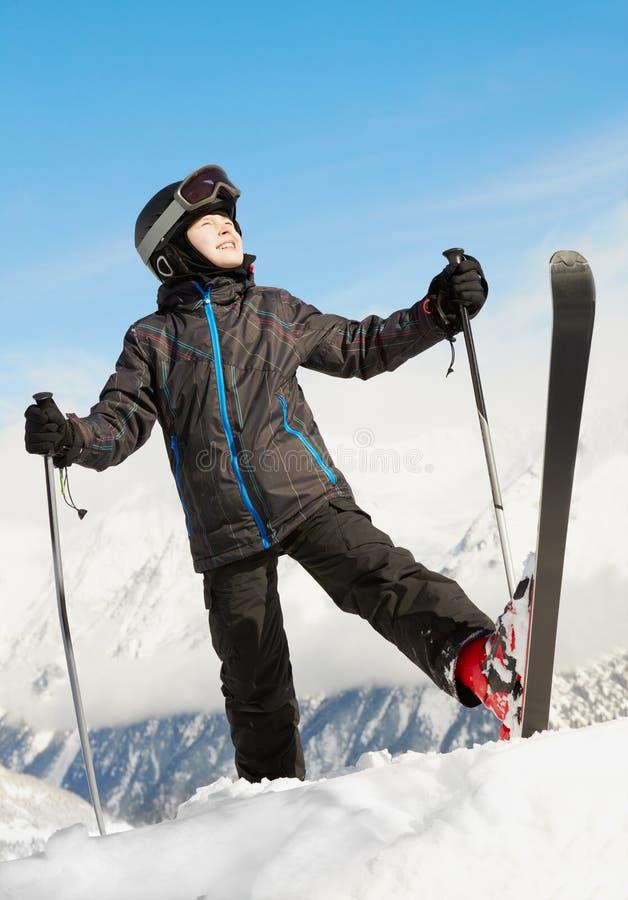 De jongen bevindt zich toenemend op één been met ski royalty-vrije stock afbeelding