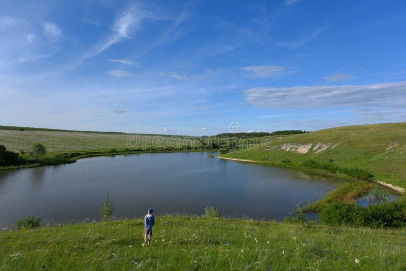 De jongen is blij en looppas aan de rivier royalty-vrije stock afbeeldingen