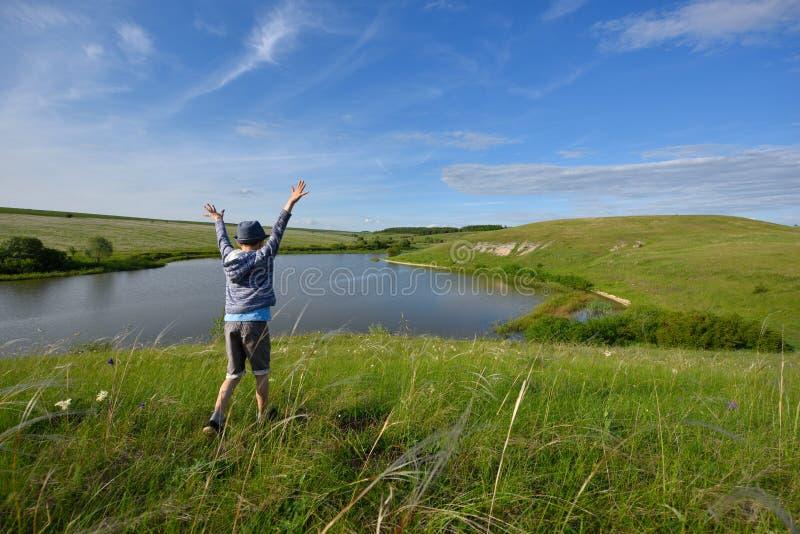 De jongen is blij en looppas aan de rivier royalty-vrije stock fotografie