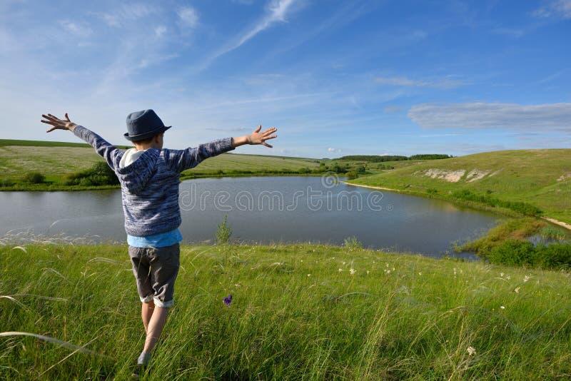 De jongen is blij en looppas aan de rivier royalty-vrije stock foto's