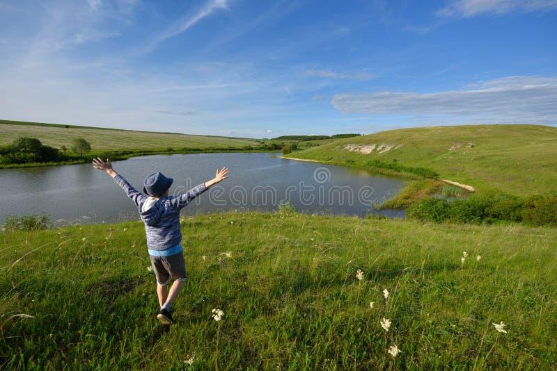 De jongen is blij en looppas aan de rivier stock afbeelding