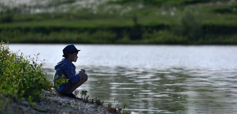 De jongen is blij en looppas aan de rivier stock fotografie