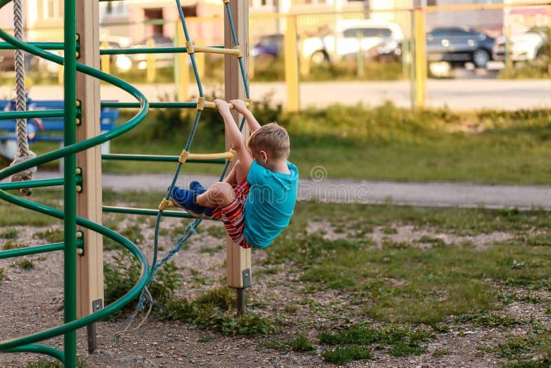 de jongen in borrels beklimt in de zomer op de Speelplaats royalty-vrije stock afbeeldingen