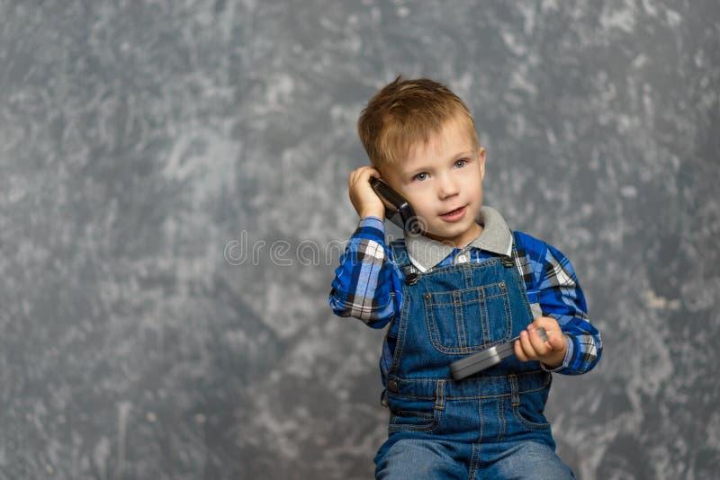 De jongen in de bouwglazen krast zijn hoofd royalty-vrije stock fotografie