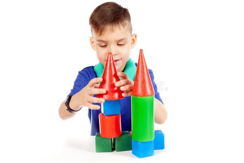 De jongen bouwt een huis van kubussen stock afbeelding