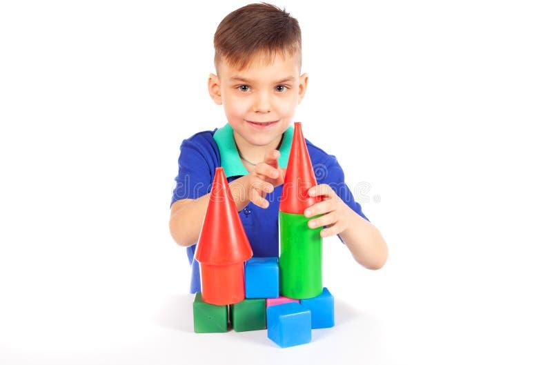 De jongen bouwt een huis van kubussen stock foto