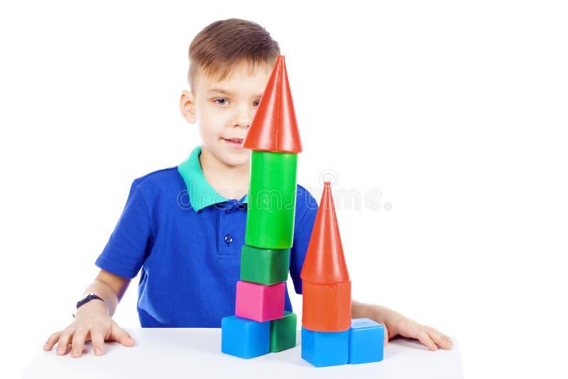 De jongen bouwt een huis van kubussen stock fotografie