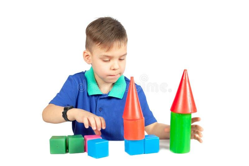 De jongen bouwt een huis van kubussen stock foto's