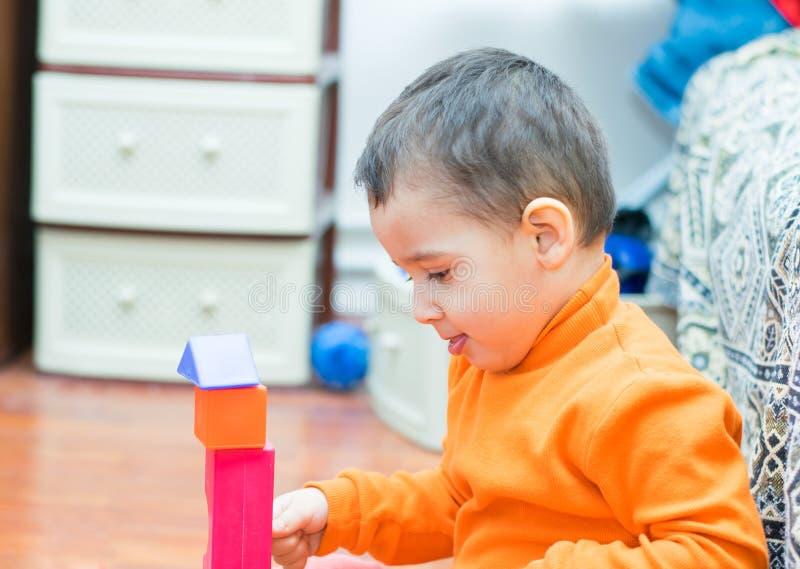 De jongen bouwt een toren stock afbeeldingen