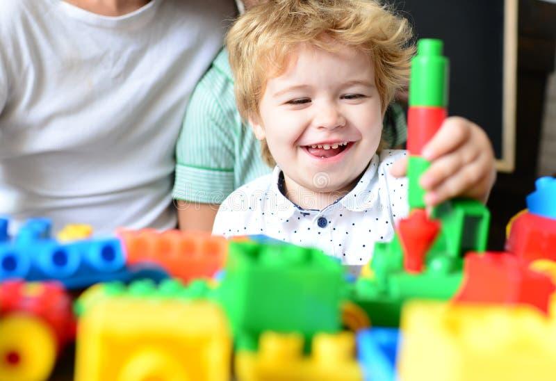 De jongen brengt prettijd in speelkamer door Kind met vrolijk gezicht royalty-vrije stock afbeeldingen