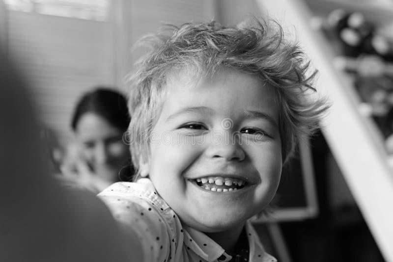 De jongen brengt prettijd in speelkamer door Kind met vrolijk gezicht stock foto