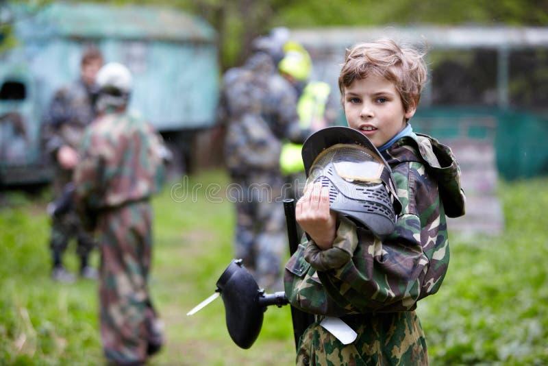 De jongen in camouflage houdt tegen een vat van het paintballkanon stock afbeelding
