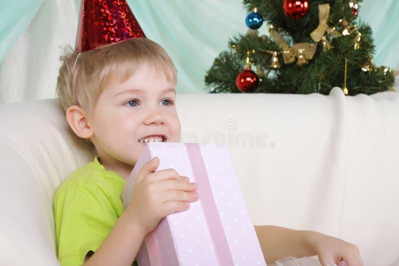 De jongen dichtbij aan Kerstmis bont-boom zit met gift stock afbeelding