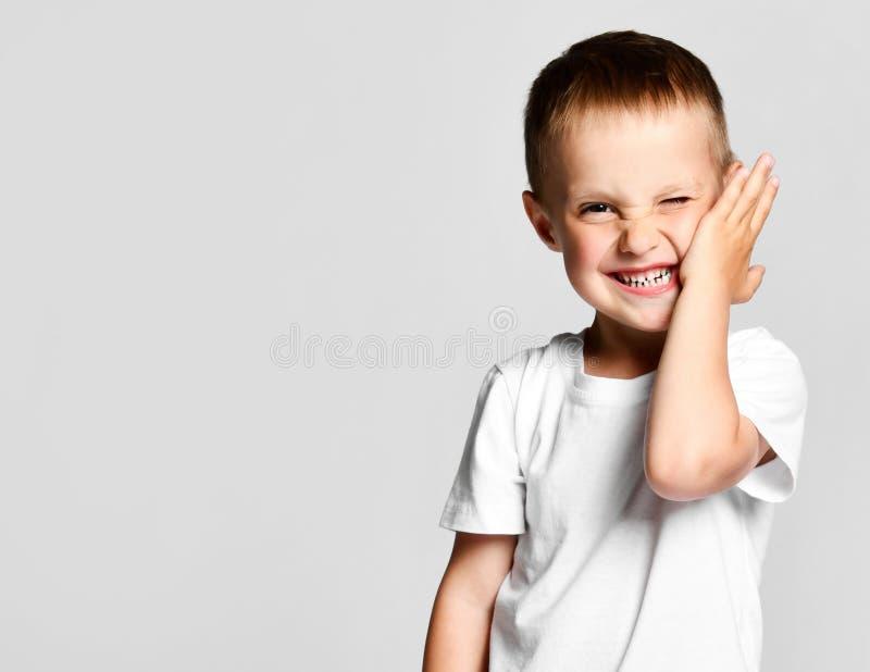 De jongen die de camera bekijkt, zette zijn palm op zijn wang, aarzelt en lacht bij de persoon die is gezien stock fotografie