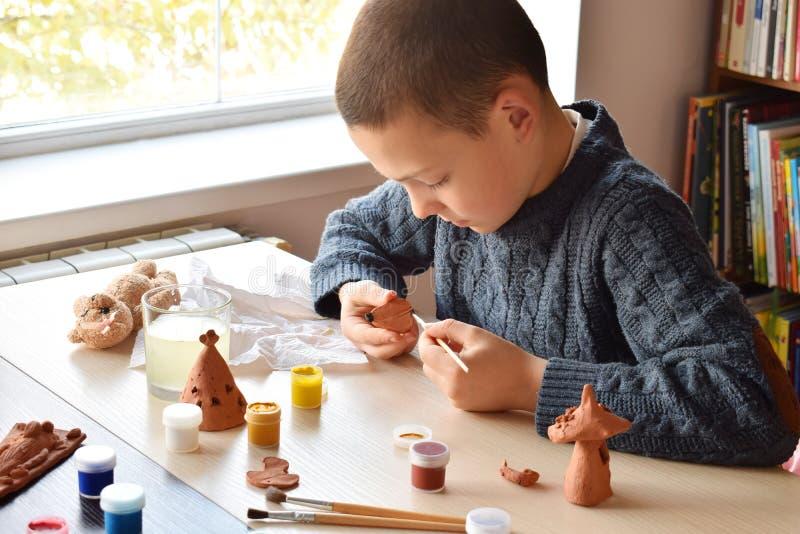 De jongen die ceramisch speelgoed maken, schildert een stuk speelgoed van de aardewerkklei met gouache Ondersteunende creativitei stock foto's