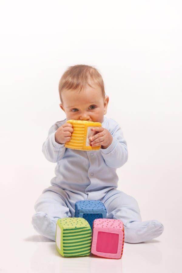 De jongen die van de baby in blauwe pyjama met kleurenblokken speelt stock foto
