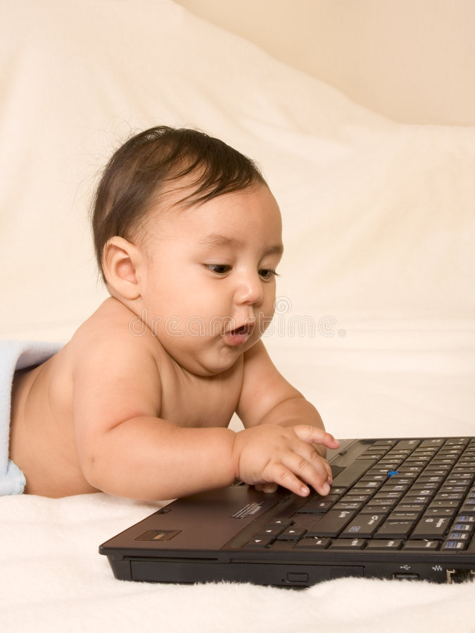 De jongen die van de baby e-mail controleert op zijn ouderslaptop royalty-vrije stock afbeeldingen