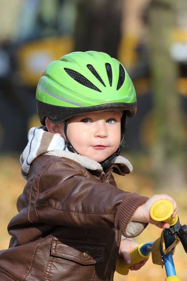 De jongen die van de baby in helm op fiets leert te berijden royalty-vrije stock foto's