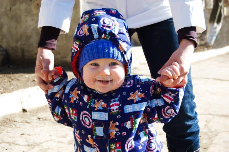 De jongen die van de baby zijn eerste stappen maakt stock foto