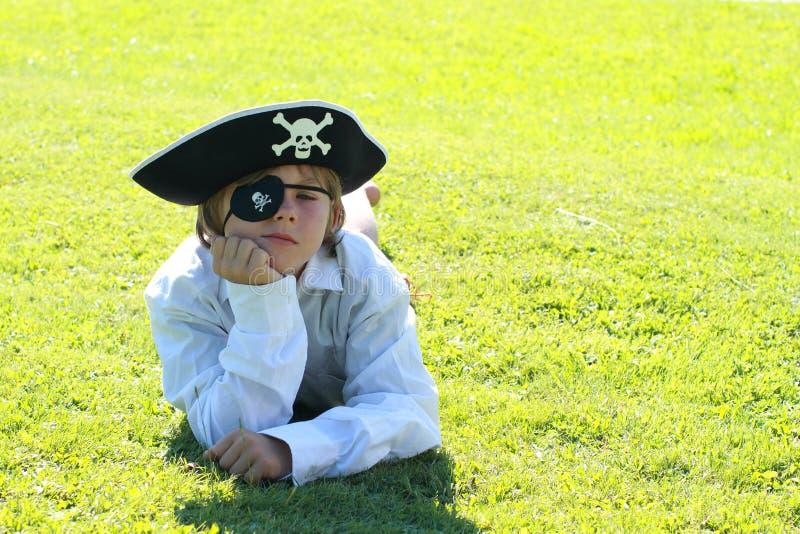 De jongen die van de piraat op gras ligt stock foto