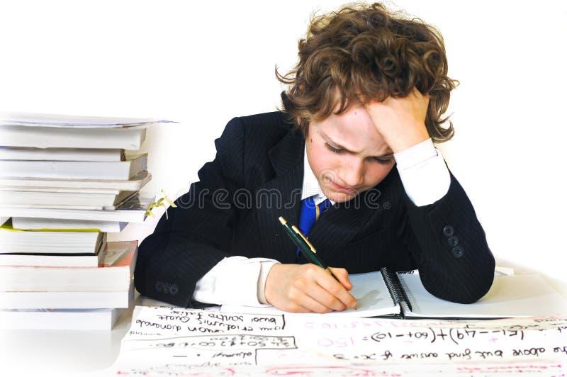 De jongen die van de school hard werkt stock afbeeldingen