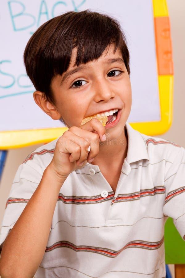 De jongen die van de school van zijn lunchmaaltijd geniet stock foto's