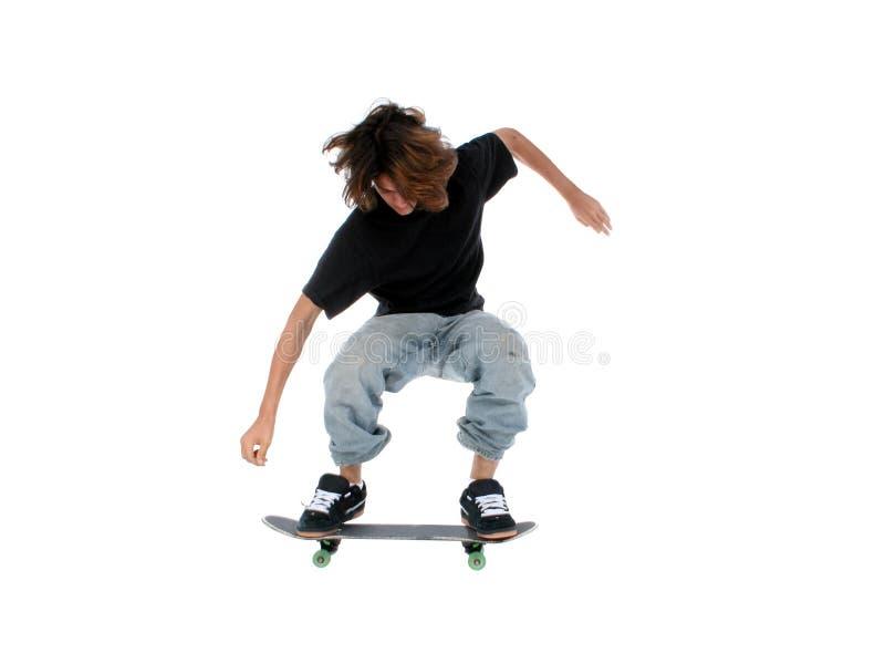 De Jongen die van de tiener met Skateboard over Wit springt stock afbeeldingen