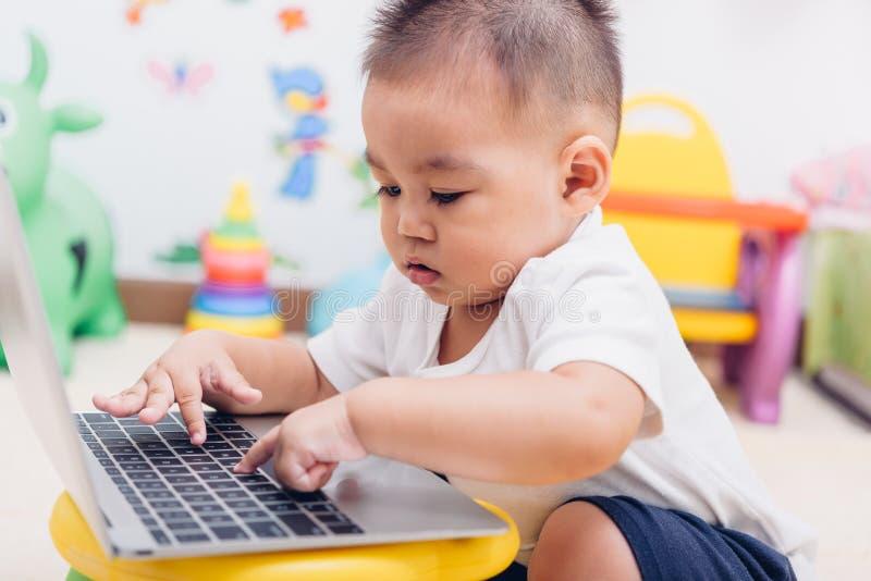 De jongen die van de kindbaby gebruikend laptop computer werken royalty-vrije stock afbeelding
