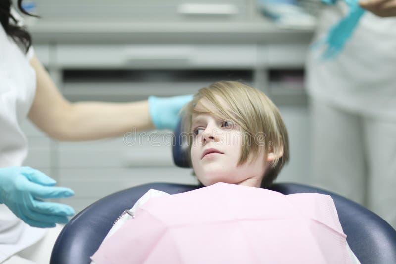 De jongen die van de schoolleeftijd als tandvoorzitter liggen stock afbeelding