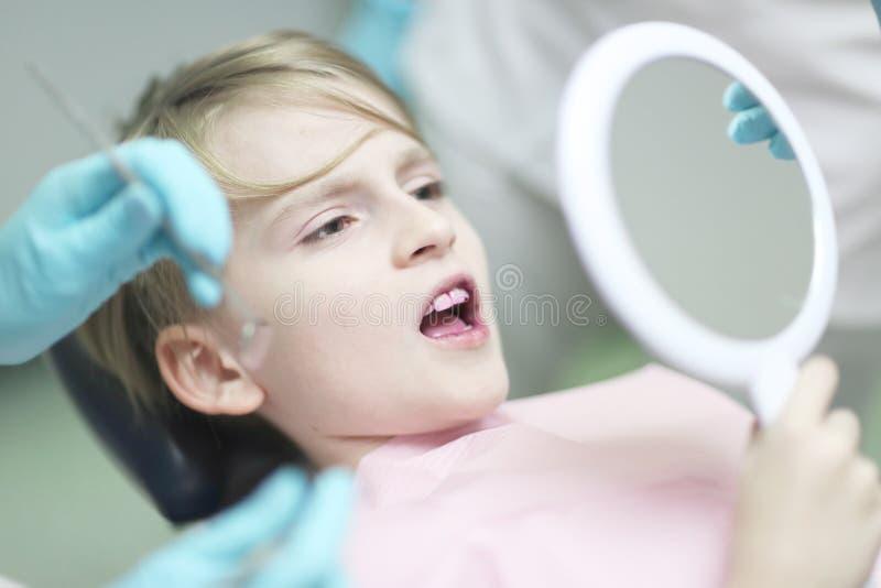 De jongen die van de schoolleeftijd als tandvoorzitter liggen royalty-vrije stock afbeeldingen