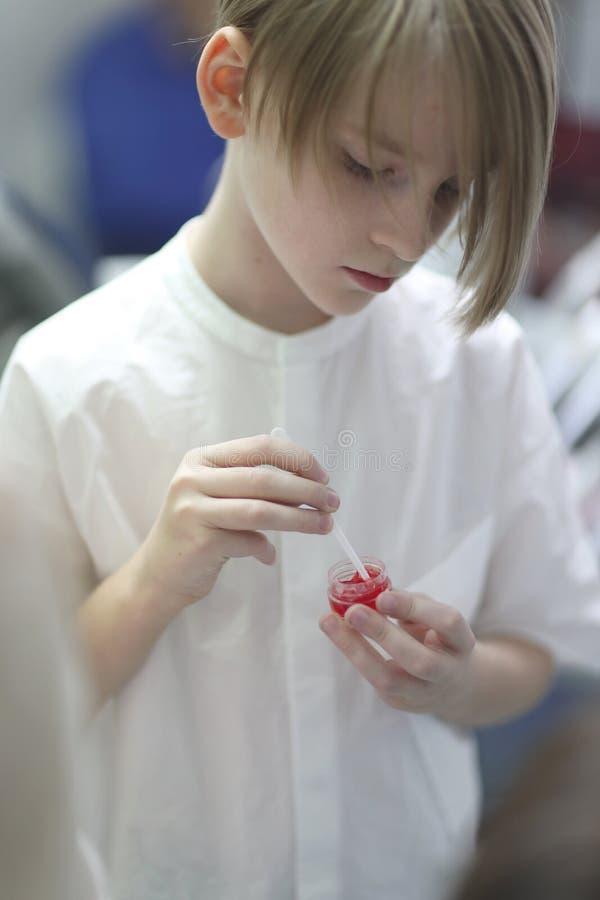 De jongen die van de schoolleeftijd een kruik geltandpasta houden stock fotografie