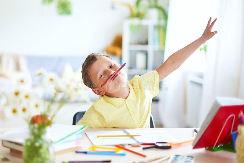 De jongen doet thuis zijn thuiswerk het gelukkige kind bij de lijst met school levert grappige glimlachen en rimpelt neus stock afbeeldingen