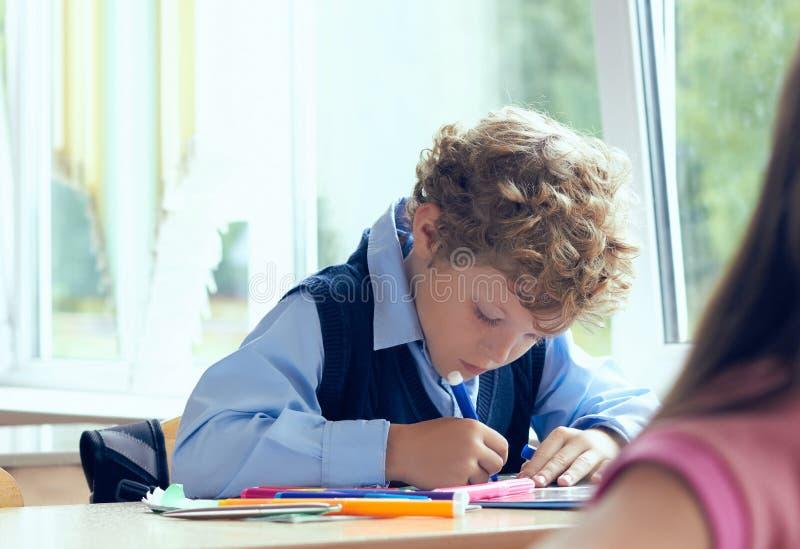 De jongen doet vastbesloten de lessenoefening tijdens de les van lage school Onderwijs en kinderjarenconcept stock afbeeldingen