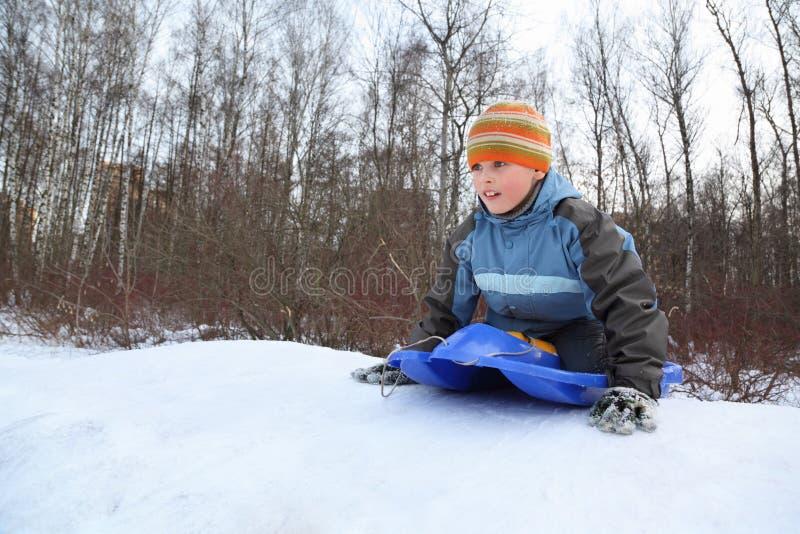 De jongen door duw is weg aandrijving van heuvel in de winter van plan stock afbeelding