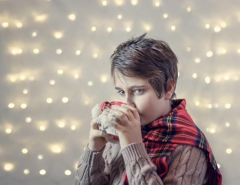 De jongen drinkt hete chocolade van een kop stock fotografie