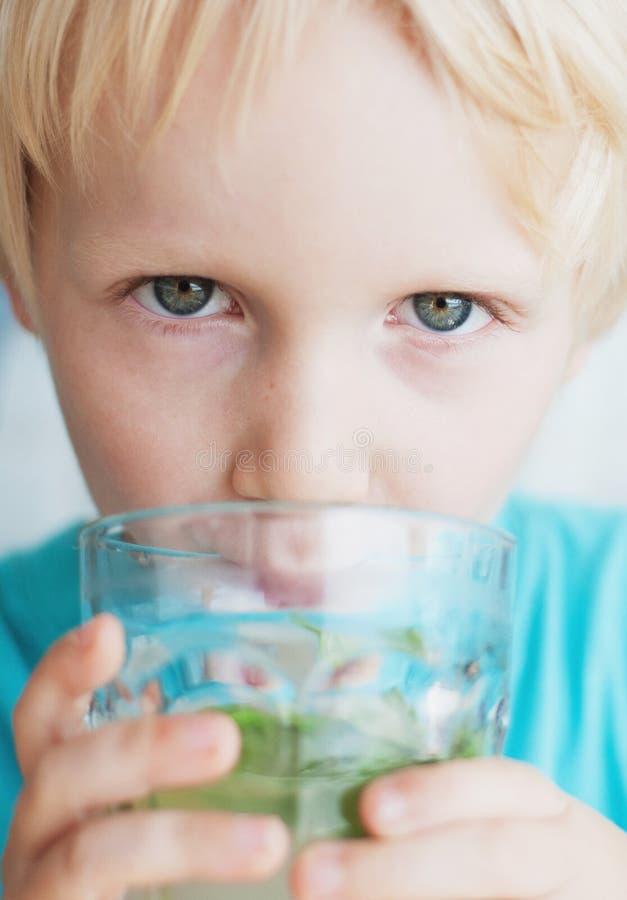 De jongen drinkt water met munt en kalk stock afbeeldingen