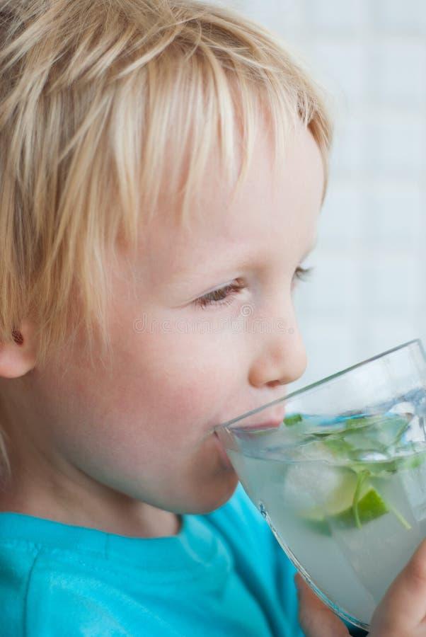 De jongen drinkt water met munt en kalk stock afbeelding