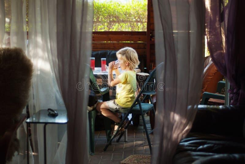 De jongen drinkt water op veranda royalty-vrije stock fotografie