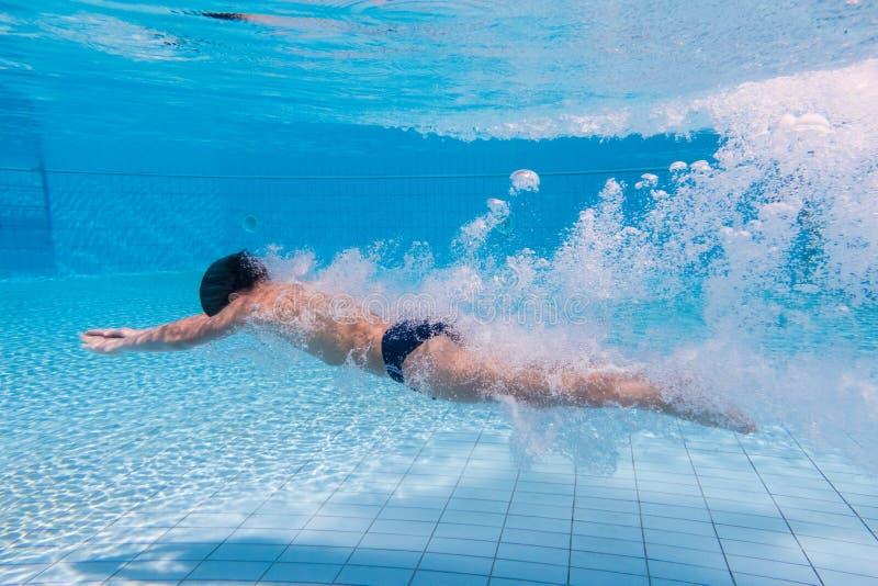De jongen duikt in zwembad royalty-vrije stock foto