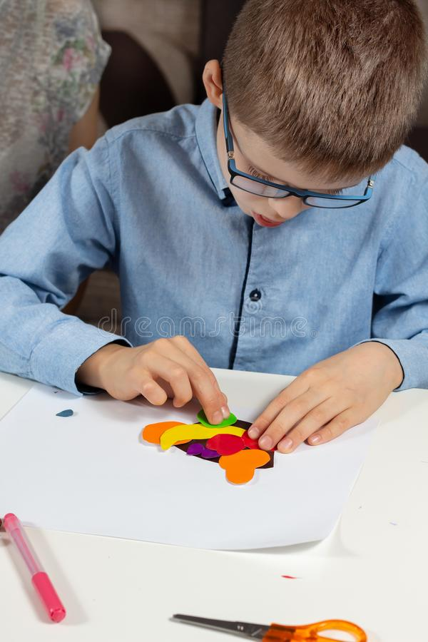 De jongen in een blauw overhemd en glazen zit bij een wit bureau en lijmt gekleurde fruitvormen van een gekleurd document aan een stock afbeelding