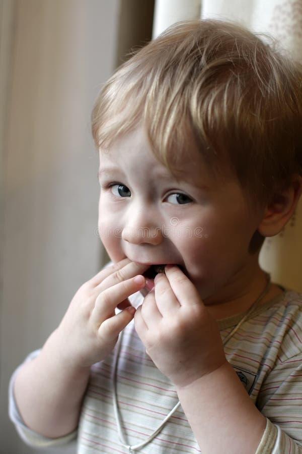 De jongen eet brood stock foto