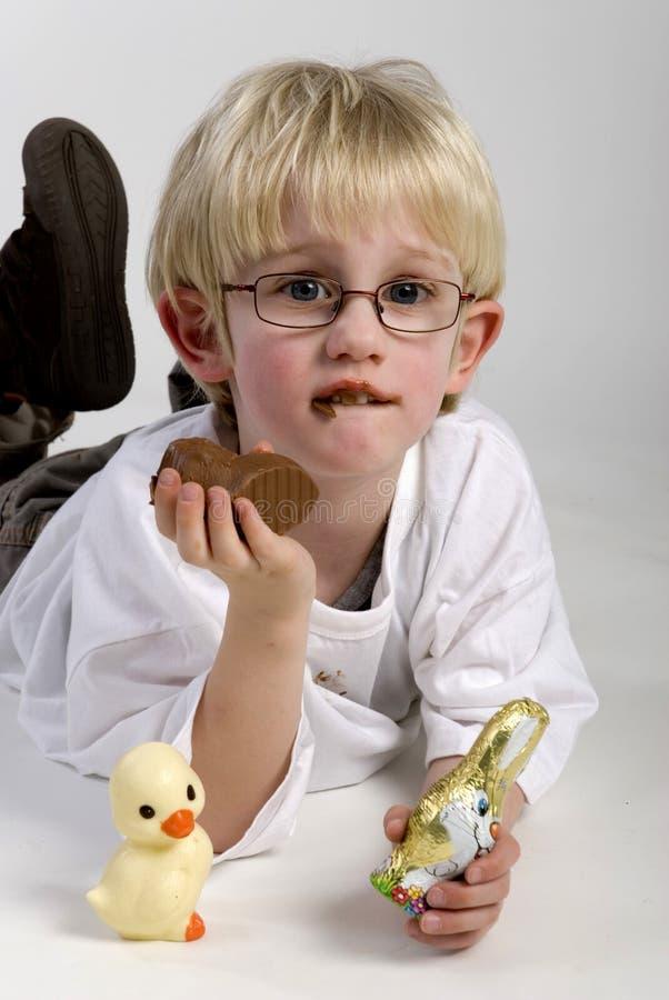 De jongen eet chocoladehazen royalty-vrije stock fotografie
